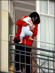 Michael Jackson dangles his baby